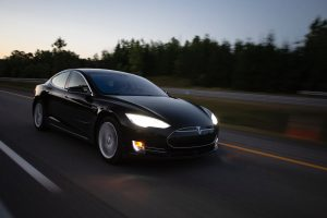 Tesla car driving at fast pace high speed on an empty road